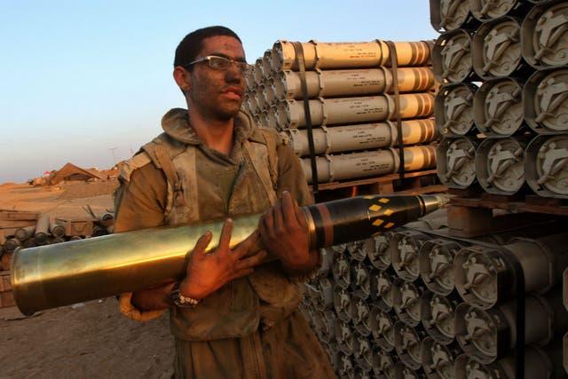 Un soldado israelí se prepara para introducir un cohete explosivo como carga de un tanque en las afueras de Gaza