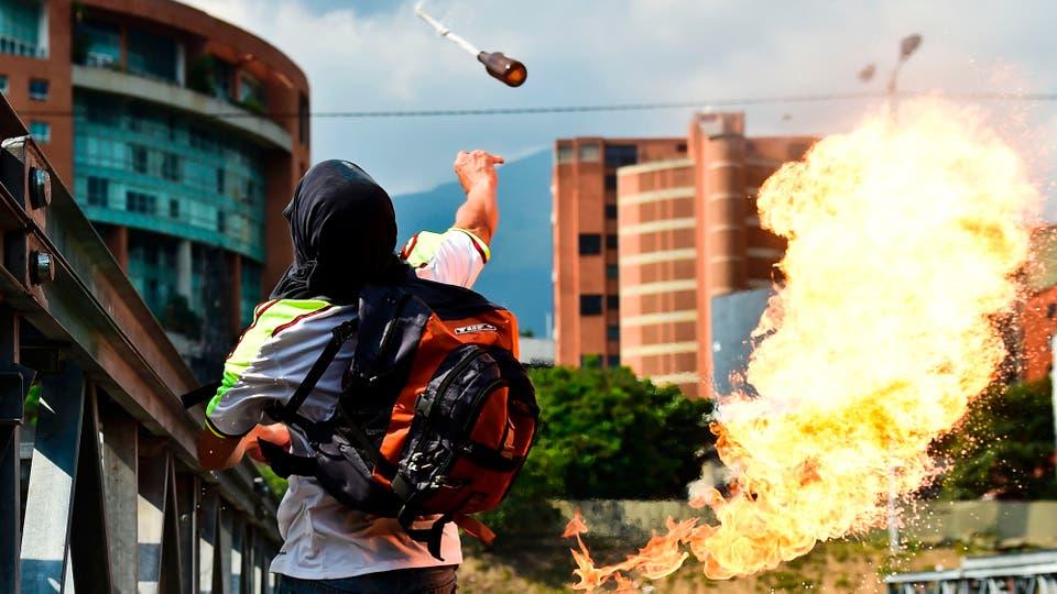 Un joven arroja una bomba molotov. Foto: AFP / Ronaldo Schemidt