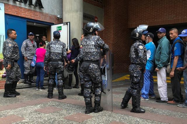 Policías vigilan la entrada de un supermercado en Caracas para evitar saqueos