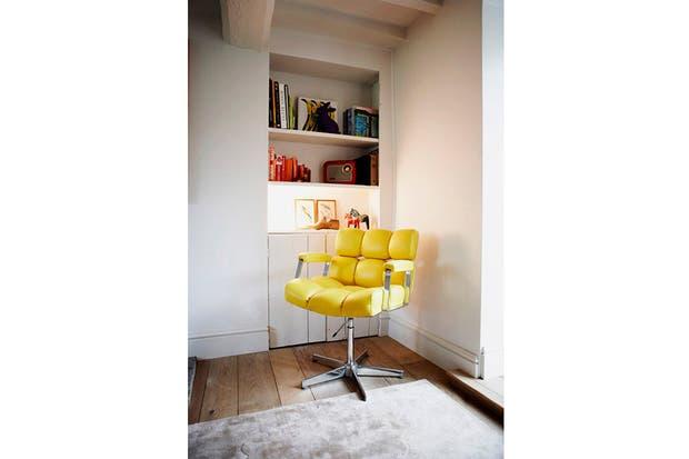 Este sillón me recuerda a los antiguos de peluquería. Sobre los estantes, algunos objetos retro, como la radio roja..