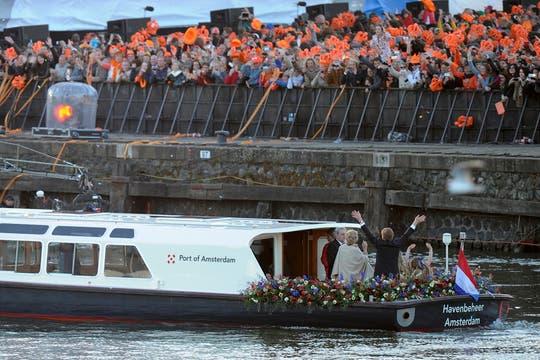 Los reyes de Holanda navegan por el río Ij en una fiesta de música y color.