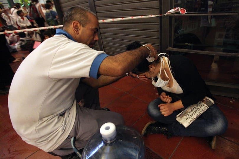 Un hombre asiste a una jóven descompuesta en la estación de Retiro. Foto: LA NACION / Silvana Colombo