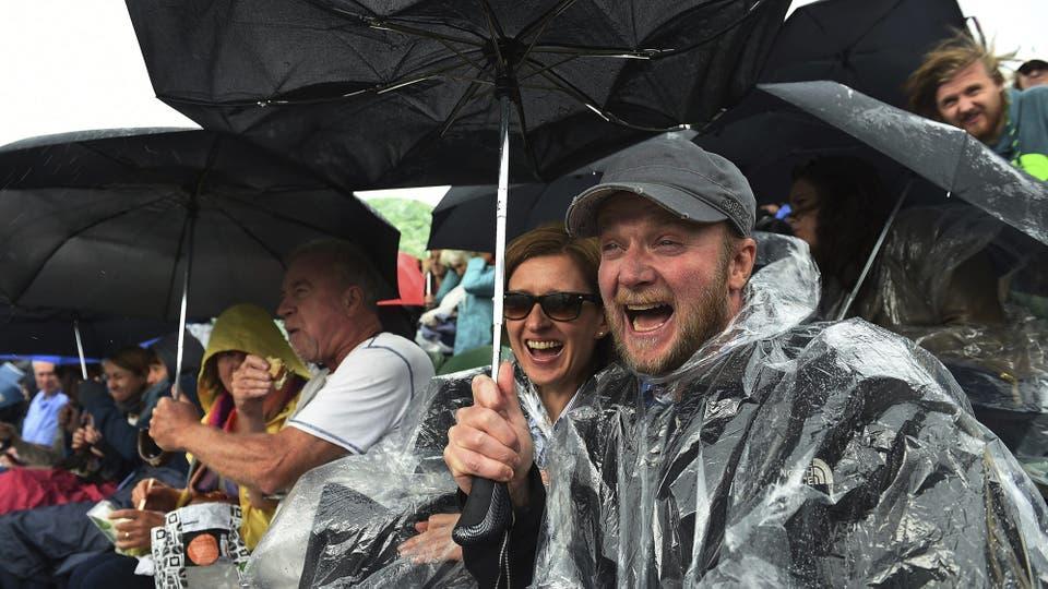 El público se protege de la lluvia que, una vez más, obligó  a retrasar Los Partidos, en el quinto día del Torneo de tenis de Wimbledon hoy, 1 de julio de 2016. Foto: EFE / ANDY RAIN
