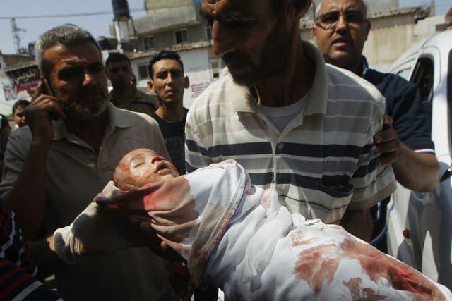 Un padre carga a su hijo herido para llevarlo a un puesto sanitario en medio de un bombardeo israelí en Gaza