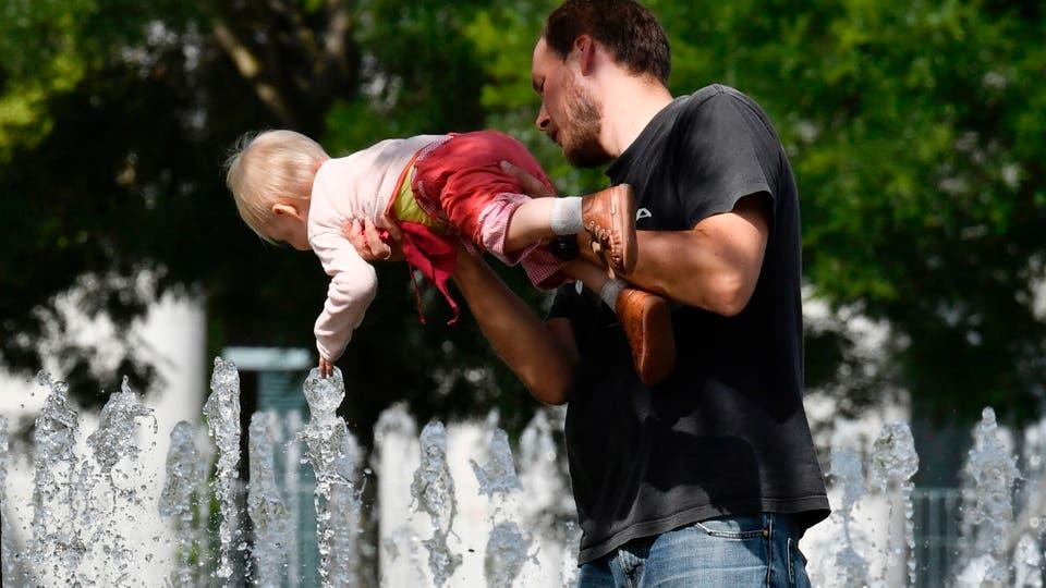 Un hombre juega con su hijo y lo refresca en una fuente de Berlín, Alemania. Foto: AFP