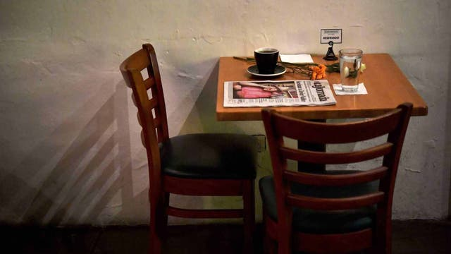 Una taza de café, agua y el diario con la historia de su muerte en la mesa del café que frecuentaba Javier, el 16 de mayo de 2017