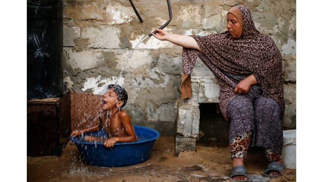 Una mujer palestina baña a su hijo con agua de un tanque, llenado por una organización benéfica, dentro de su vivienda en Khan Younis, en el sur de la Franja de Gaza
