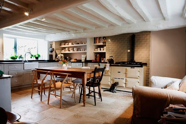 En la cocina se destacan los azulejos beige colocados como ladrillos. Los estantes y la bacha de campo son algunos de los toques en este espacio..