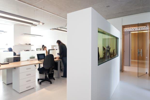 e trata de un espacio grande con varios puestos de trabajo, donde la primacía del blanco contribuye a generar un ambiente despejado y fresco..