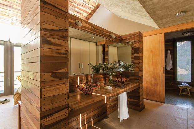 En el baño, mesada en madera con bacha de vitrofusión. En su juego de ángulos y alturas, el techo contiene el lucernario, que permite aprovechar al máximo la luz natural..