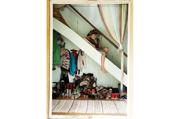 Margaux sentada en la escalera que lleva a los cuartos: la pared conserva el tono azul 'Tiffany'' que tenía cuando se mudaron..