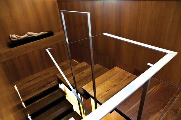 La escalera que parte del pasillo al que se llega trasponiendo la puerta de entrada avanza sutilmente hacia la planta alta rodeada de paneles de vidrio templado coronados con terminaciones de acero..