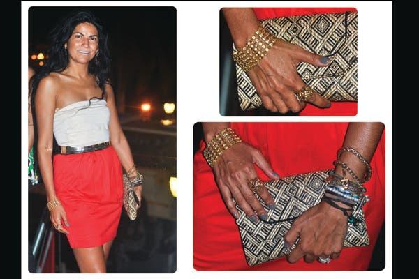Un clutch de rafia, cinturón metálico y pulseras de cadenas son los accesorios elegidos para combinar con esta falda rojo fuego y strapless blanco. Foto: Lulu Biaus