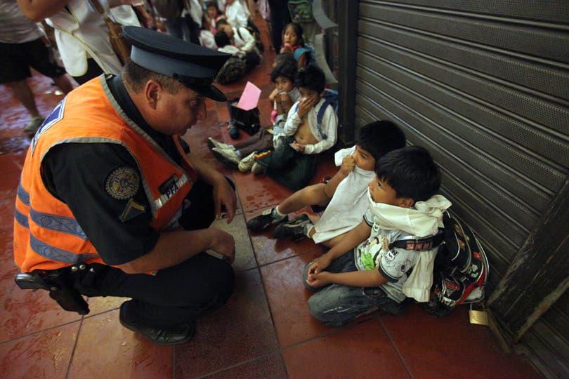Un policía brinda contención a varios niños afectados. Foto: LA NACION / Silvana Colombo