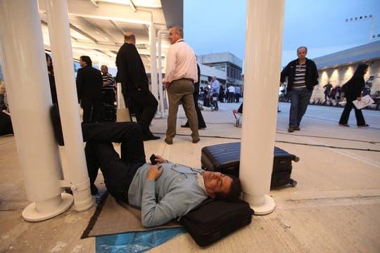 Un hombre descansa en el suelo mientras espera la salida de su vuelo. Foto: LA NACION / Soledad Aznarez