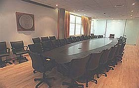 La sala de Junta Ejecutiva para 30 personas: mesa con terminación de laqueado negro opaco con sobretapa de cuero negro y sillas negras