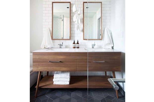 Un antiguo mueble de madera cobra vida al transformarse en el punto focal de este moderno baño.  /Onekindesign.com
