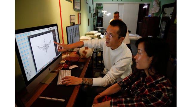 Eason Zhou, de 28 años, madre de un niño de 5 años, revisa un diseño de tatuaje en una computadora con su tatuador Shi Hailei en Shanghai