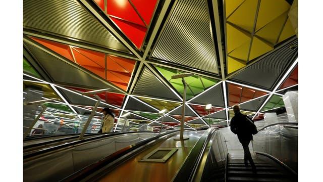 La gente sube a las escaleras mecánicas en la estación de metro Sretensky Bulvar en Moscú, Rusia