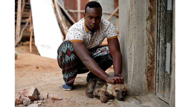 Abbas Yusuf, de 23 años, juega con un cachorro de hiena cerca de su casa