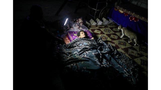 Una mujer discapacitada yace en una cama mientras un pariente la ilumina con una linterna para que el fotógrafo la vea durante un corte de luz en Khan Younis, en el sur de la Franja de Gaza