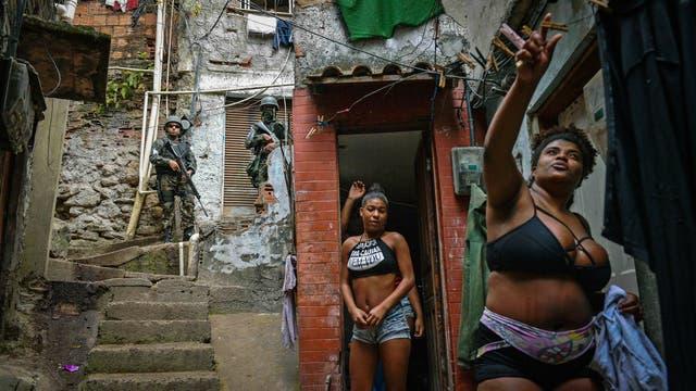 Una mujer cuelga la ropa mientras policías militarizados vigilan en la favela de Rocinha en Río de Janeiro