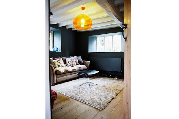 En la sala de estar, el toque de color aparece en la lámpara naranja. Me gusta la banqueta típica de oficina con pie metálico y tapizada en cuero negro..