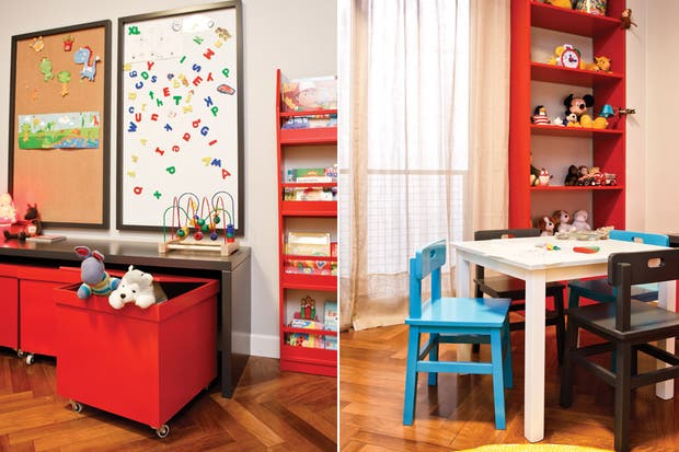 El mueble laqueado en color gris brinda un nicho donde guardar los jugueteros de color rojo con ruedas, de donde se asoma un conejo tejido al crochet (El Circulo de las Vitaminas)..