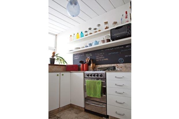 Los estantes amurados fueron diseñados por la dueña de casa, al igual que las banquetas. El techo es de losetas de hormigón, una opción especialmente económica y práctica por la velocidad en su colocación..