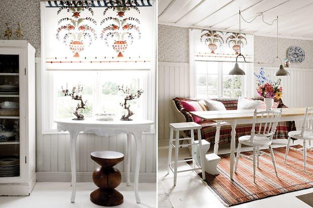 Bajo la ventana con una cortina romana con motivo vintage escandinavo pintada a mano (Gysinge), un antiguo sofá vestido con mantas y almohadones oficia de banqueta complementado con sillas blancas (Form 1900)..