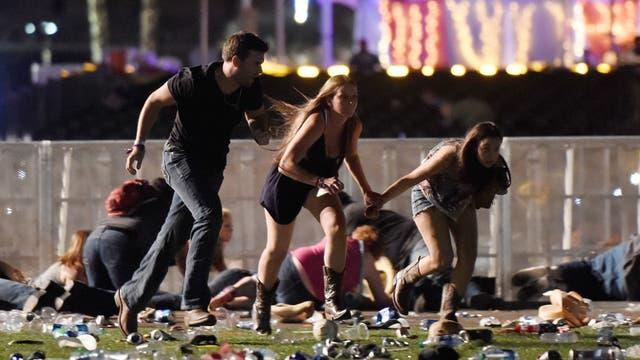 Tres asistentes al festival de música country en Las Vegas intentan refugiarse de la lluvia de balas disparadas desde el hotel Mandalay Bay