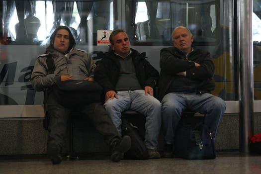 Tres hombres esperan a que se reanuden los vuelos siuspendidos por la nube de ceniza volcánica. Foto: LA NACION / Ricardo Pristupluk
