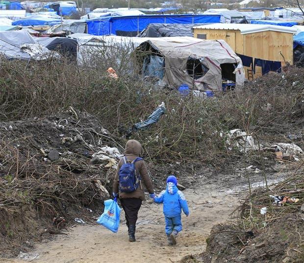 Un migrante y su hijo caminan por la llamada 'jungla' de Calais, en Francia
