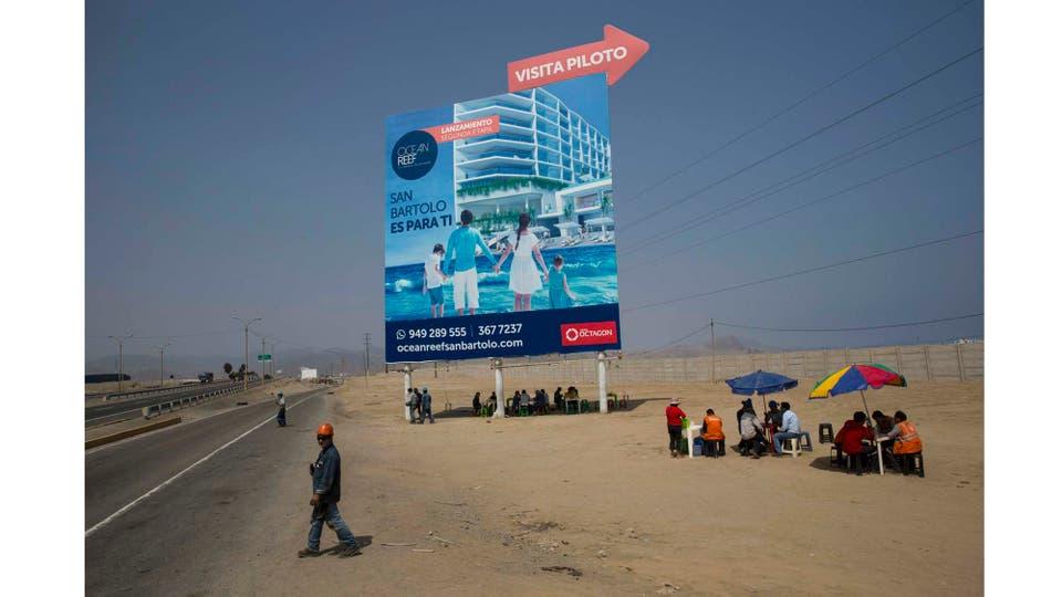 Trabajadores almuerzan a la sombra de un gigantesco cartel de publicidad en un vecindario pobre de la zona sur de Lima