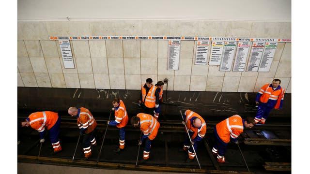 Empleados traban en la reparación de la vía férrea en la estación de metro Sukharevskaya en Moscú, Rusia