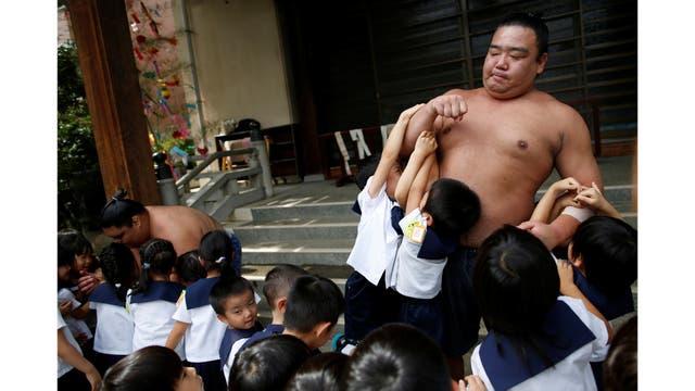 El luchador de sumo Kainoryu juega con los niños de un jardín de infantes
