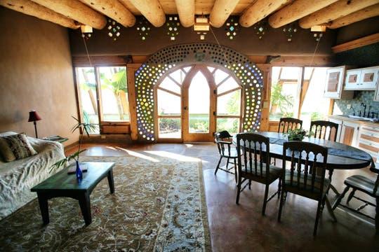 Estilo rústico y cálido en una sala de estar y comedor construidos con material sustentable. Foto: LA NACION / Gentileza fundación Michael Reynolds