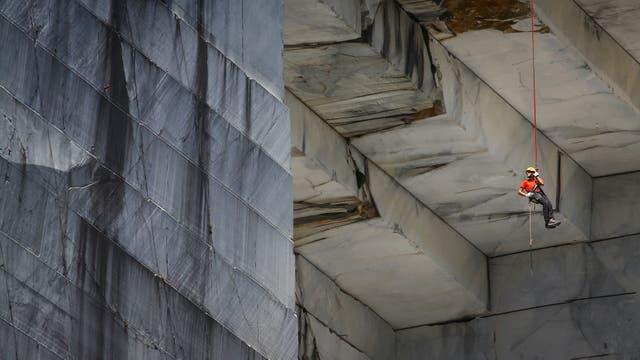 """Un trabajador, conocido como """"Tecchiaiolo"""", examina el mármol en la cantera de Cervaiole en Monte Altissimo en los Alpes Apuanos, Toscana"""