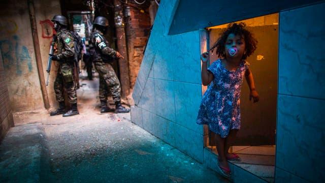 Un miembro de tácticas de combate urbano, el personal de la policía militar del ejército brasileño patrulla a lo largo de un callejón en la Rocinha