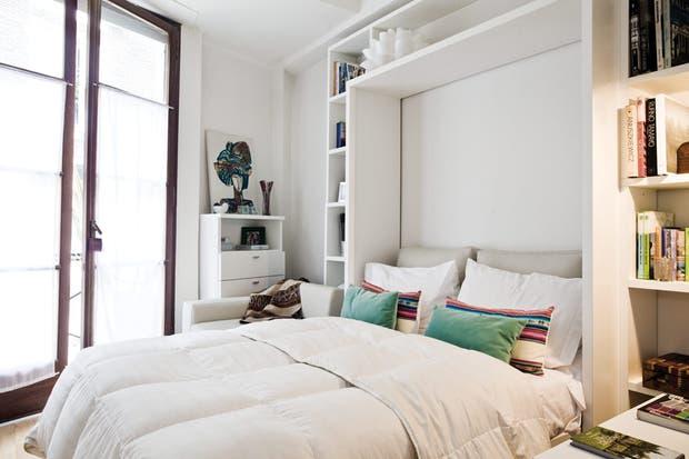 Cama rebatible y bibliotecas en melamina (Minbai) con sábanas (Blanco Arenales) y almohadones (Armonía). Lámpara blanca (Sr Mor).