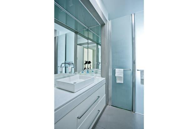 n el baño, frente a la mesada de mármol hay un jacuzzi; las dos puertas traslúcidas separan los sanitarios del box de la ducha, un esquema que la dueña de casa copió de un hotel..