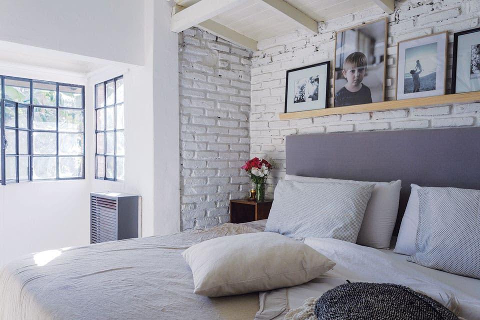 A un lado del ventanal, una pequeña expansión dio el lugar justo para la cama con respaldo de género gris y cubrecama de lino (todo de Jaus), las mesas de luz antiguas y un estante con fotos enmarcadas.  Foto:Living /Daniel Karp