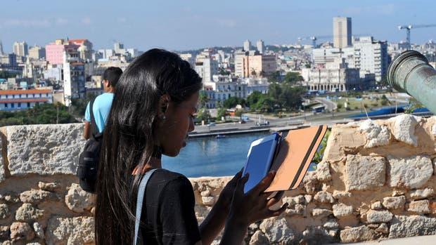 Una joven cubana lee desde su tableta en La Habana, Cuba. Con un acceso limitado a Internet, los lectores digitales de la isla comparten contenidos de forma inalámbrica vía Bluetooth