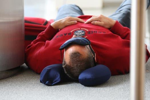Un hombre se toma una siesta en el aroparque metropolitano mientras espera que se reanuden los vueloa. Foto: LA NACION / Ricardo Pristupluk