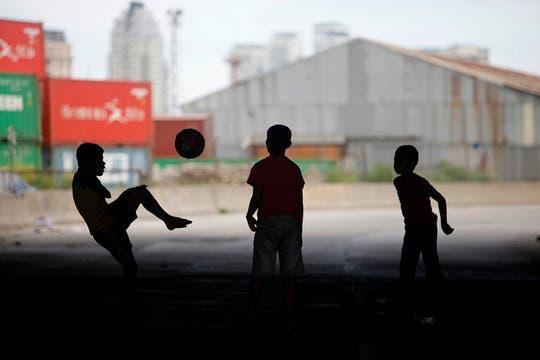Varios niños juega mientras las casas son demolidas. Foto: LA NACION / Maxie Amena