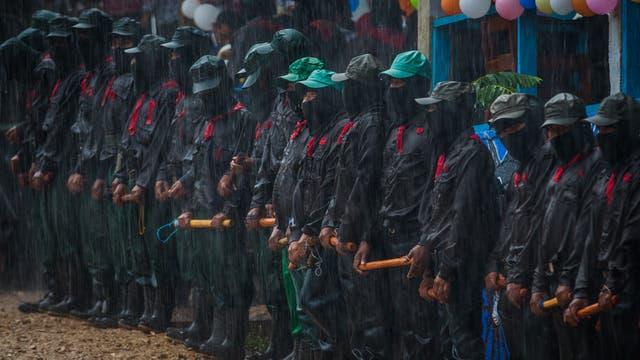 Miembros del Ejército Zapatista de Liberación Nacional (EZLN) se paran bajo la lluvia torrencial mientras brindan seguridad en un acto en La Garrucha, Chiapas