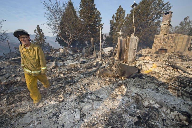 EL bombero Dennis Immel camina por los restos de la casa de su vecino que fue destruida por el fuego. Foto: AFP