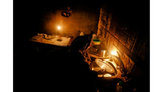 Una mujer lava los platos a la luz de las velas en el pueblo de Beit Lahiya, en el norte de la Franja de Gaza