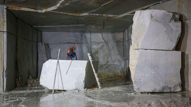 Un trabajador mide un bloque de mármol en el Monte Altissimo