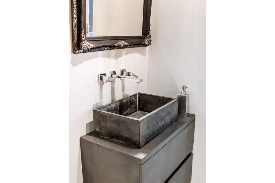 Conformando una caja con acentos plateados, el baño está revestido con cemento alisado, salvo el box de ducha, donde se usaron venecitas grises (Murvi). Un mueble laqueado con cajones ($7.500, Étude Interiorismo) sostiene la bacha. Toda la grifería es FV 'Dominique'.  Foto:Living /Santiago Ciuffo
